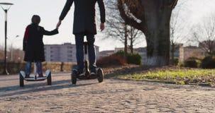 Tochterkindermädchenreiten segway mit ihrem Vati in der Stadt Moderne zukünftige Transporttechnologie Aktive Familie Parkbürgerst stock video footage