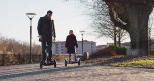 Tochterkindermädchenreiten segway mit ihrem Vati in der Stadt Moderne zukünftige Transporttechnologie Aktive Familie Parkbürgerst stock footage