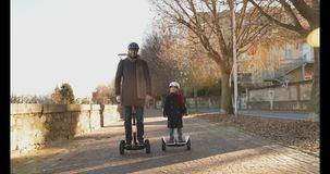 Tochterkindermädchenreiten segway mit ihrem Vati in der Stadt Moderne zukünftige Transporttechnologie Aktive Familie Parkbürgerst stock video