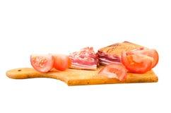 Tocino ahumado crudo en una placa de madera con los tomates Fotografía de archivo