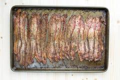 Tocino cocido del grano de pimienta adentro en bandeja del horno en el fondo de madera Fotos de archivo