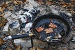 Tocino frito en un sartén Una comida campestre en el bosque Fotos de archivo