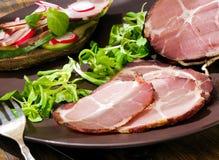 Tocino o jamón crudo, secado con el bocadillo, las verduras y las hierbas en el tablero de madera Foto de archivo libre de regalías
