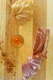Tocino, pimienta picadita y un vidrio de brandy en una placa de madera Fotografía de archivo libre de regalías