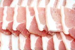 Tocino, rebanada rayada del cerdo en el fondo blanco Fotos de archivo