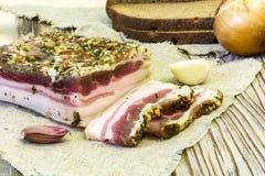 Tocino salado rústico con pan, ajo y cebollas Foto de archivo