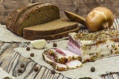 Tocino salado rústico con pan, las cebollas y el ajo Imagenes de archivo