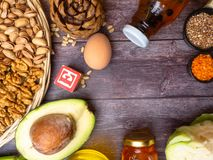 Tocopherol or vitamin E rich food in wooden board. Tocopherol or vitamin E rich food as avocado, nuts, apricot, raisin, oil,celery, cabbage, lentils, buckweat royalty free stock photography