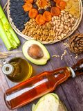 Tocopherol or vitamin E rich food in wooden board. Tocopherol or vitamin E rich food as avocado, nuts, apricot, raisin, oil,celery, cabbage, lentils, buckweat royalty free stock photo