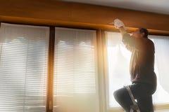 Tocznej żaluzi naprawiacz Pracownik, z rękawiczkami i śrubokrętem, przystosowywa łamaną rolkową żaluzję dom Zdjęcie Stock