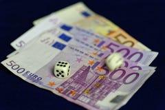 Toczni kostka do gry na ułożonych Euro banknotach Fotografia Stock
