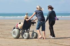 Toda a cadeira de rodas da praia do terreno faz praias acessíveis imagem de stock royalty free