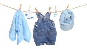 Toda la ropa del muchacho que cuelga en una cuerda para tender la ropa Foto de archivo libre de regalías