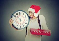 A toda prisa mujer subrayada que lleva el sombrero de Papá Noel que sostiene la caja de regalo del reloj fotos de archivo