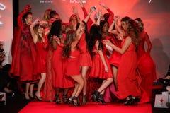 Todas as celebridades dançam em palco na pista de decolagem no vermelho ir para a coleção vermelha 2015 do vestido das mulheres Foto de Stock