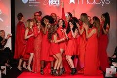 Todas as celebridades dançam na fase na pista de decolagem no vermelho ir para a coleção vermelha 2015 do vestido das mulheres Foto de Stock
