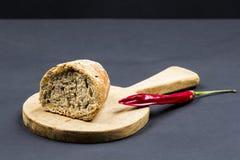 Todavía composición de la vida con la tabla de cortar de madera de la cocina, el pan y la pimienta roja Fotografía de archivo libre de regalías