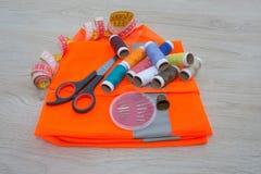 Todavía costura de vida: paño colorido El equipo de costura incluye los hilos de diversos colores, del dedal y de otros accesorio Foto de archivo