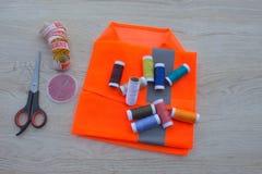 Todavía costura de vida: paño colorido las tijeras y el equipo de costura incluye los hilos de diversos colores, del dedal y del  Imágenes de archivo libres de regalías