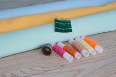 Todavía costura de vida: paño colorido las tijeras y el equipo de costura incluye los hilos de diversos colores, del dedal y del  Fotos de archivo libres de regalías