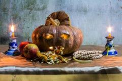 Todavía de Halloween vida con las calabazas, la manzana, las velas y el rosario Fotografía de archivo