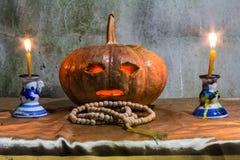 Todavía de Halloween vida con las calabazas, las velas y el rosario Imagenes de archivo