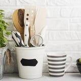 Todavía de la cocina vida en un fondo blanco de la pared de ladrillo: diversas tablas de cortar, herramientas, verdes para cocina Foto de archivo libre de regalías