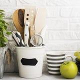 Todavía de la cocina vida en un fondo blanco de la pared de ladrillo: diversas tablas de cortar, herramientas, verdes para cocina Foto de archivo