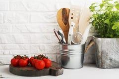 Todavía de la cocina vida en un fondo blanco de la pared de ladrillo: diversas tablas de cortar, herramientas, verdes para cocina Imagen de archivo libre de regalías