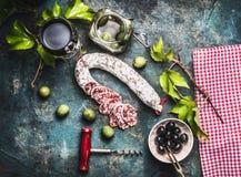 Todavía de la comida vida italiana con el vidrio del vino rojo, de aceitunas y de la salchicha en fondo rústico Imágenes de archivo libres de regalías