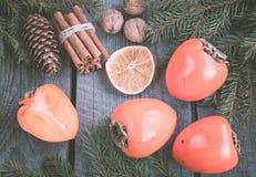 Todavía de la Navidad vida con el caqui y el canela con el abeto en fondo de madera Visión superior Imagen de archivo