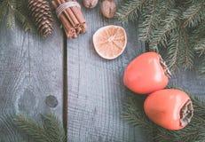 Todavía de la Navidad vida con el caqui y el canela frescos con el abeto en fondo de madera Visión superior Fotografía de archivo libre de regalías