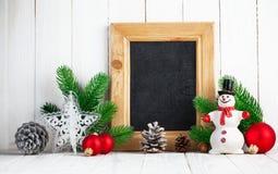 Todavía de la Navidad vida con el muñeco de nieve y el abeto en el tablero de madera Fotografía de archivo libre de regalías