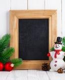 Todavía de la Navidad vida con el muñeco de nieve y el abeto en el tablero de madera Fotos de archivo