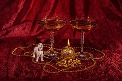 Todavía de la Navidad vida con los vidrios, perro esférico de la vela en el fondo de Borgoña Imagenes de archivo