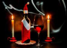 Todavía de la Navidad vida con una botella de vino, las velas y los glas de un vino Imagen de archivo libre de regalías