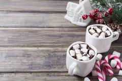 Todavía de la Navidad vida - dos tazas de chocolate caliente con la melcocha, los caramelos, la casa del juguete y la rama del ab Imagen de archivo