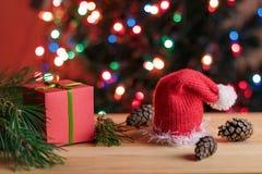 Todavía de la Navidad vida: el regalo rojo de la caja, pino ramifica, sombrero rojo de la Navidad, conos del pino Fotos de archivo libres de regalías