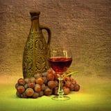 Todavía de la obscuridad vida - botella, vidrio y uvas de la arcilla imagen de archivo