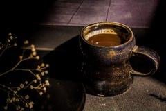 Todavía de la oscuridad taza de café del vintage de la vida y rama seca Fotos de archivo libres de regalías
