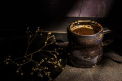 Todavía de la oscuridad taza de café del vintage de la vida y rama seca Imágenes de archivo libres de regalías