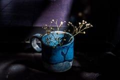 Todavía de la oscuridad vida con la taza de cerámica y la rama seca Foto de archivo