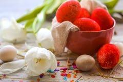 Todavía de Pascua vida con los huevos coloreados en una placa y tulipanes blancos Imagen de archivo libre de regalías