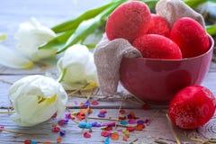 Todavía de Pascua vida con los huevos coloreados en una placa y tulipanes blancos Foto de archivo