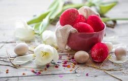 Todavía de Pascua vida con los huevos coloreados en una placa y tulipanes blancos Fotografía de archivo