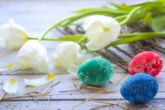 Todavía de Pascua vida con los huevos coloreados y los tulipanes blancos Imagen de archivo libre de regalías