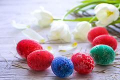 Todavía de Pascua vida con los huevos coloreados y los tulipanes blancos Imágenes de archivo libres de regalías