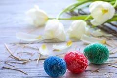 Todavía de Pascua vida con los huevos coloreados y los tulipanes blancos Imagen de archivo
