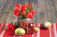 Todavía de Pascua vida con los tulipanes rojos, el regalo envuelto y los huevos de Pascua Foto de archivo