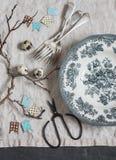 Todavía de Pascua vida Placa del vintage, bifurcación, tijeras, huevos de codornices, guirnalda de papel, ramas en una tabla gris fotografía de archivo libre de regalías